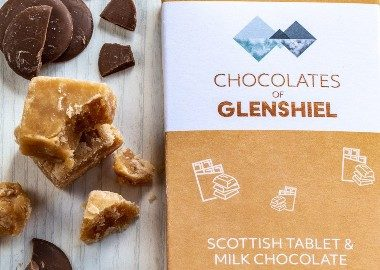 Chocolates of Glenshiel Scottish tablet milk chocolate bar sitting next to pieces of tablet and chocolate