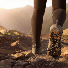 Lower legs and walking shoes of a person hiking on uneven terrain - charity walk