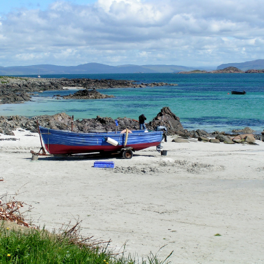 Beach on Iona with a fishing boat during summertime in Scotland